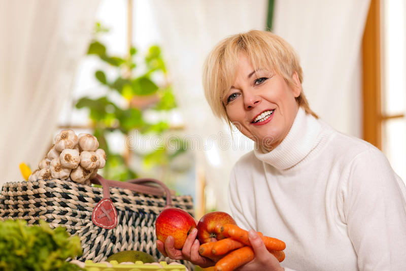Woman with groceries. She just shopped, putting them on the kitchen table royalty free stock photography
