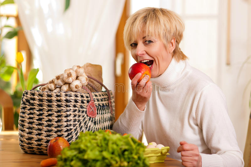 Woman with groceries eating apple. Woman with groceries she just shopped, eating an apple on the spot stock photo