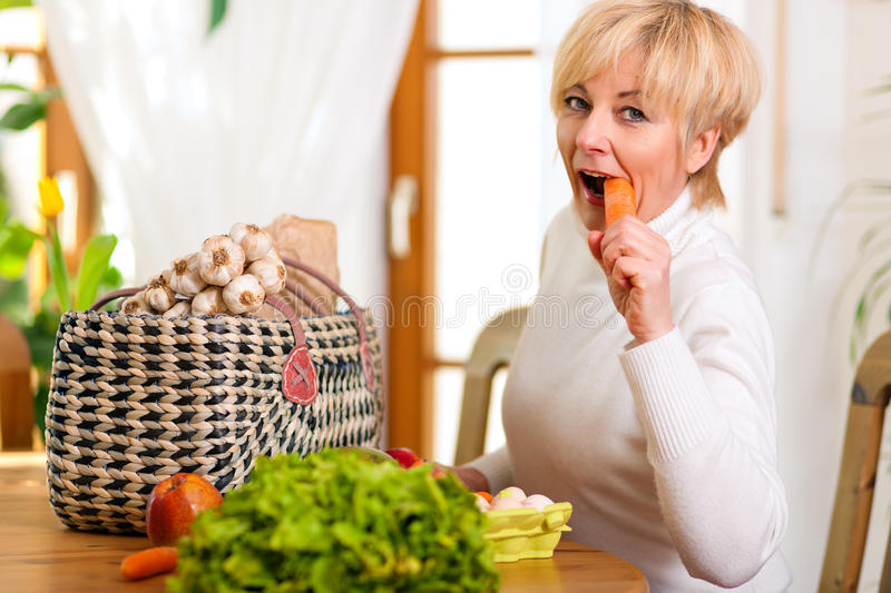 Woman with groceries eating carrot. Woman with groceries she just shopped, eating a carrot on the spot stock photo