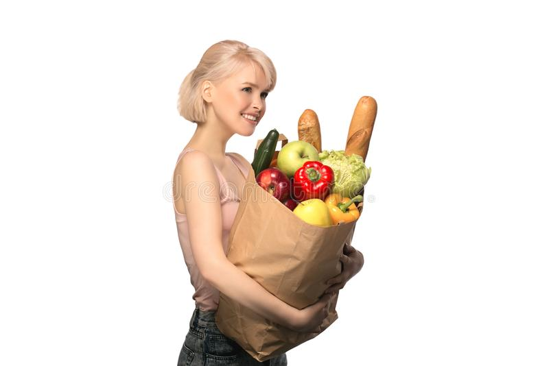 Woman with groceries shopping bag. Portrait of happy smiling woman with groceries shopping bag full of vegetables isolated on white background stock image