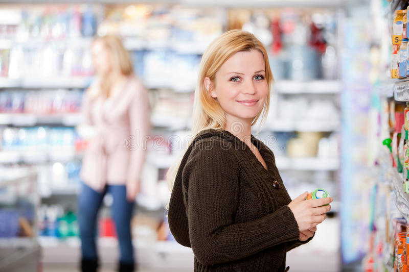 Woman in Grocery Store. A young woman buying groceries in a grocery store royalty free stock photos