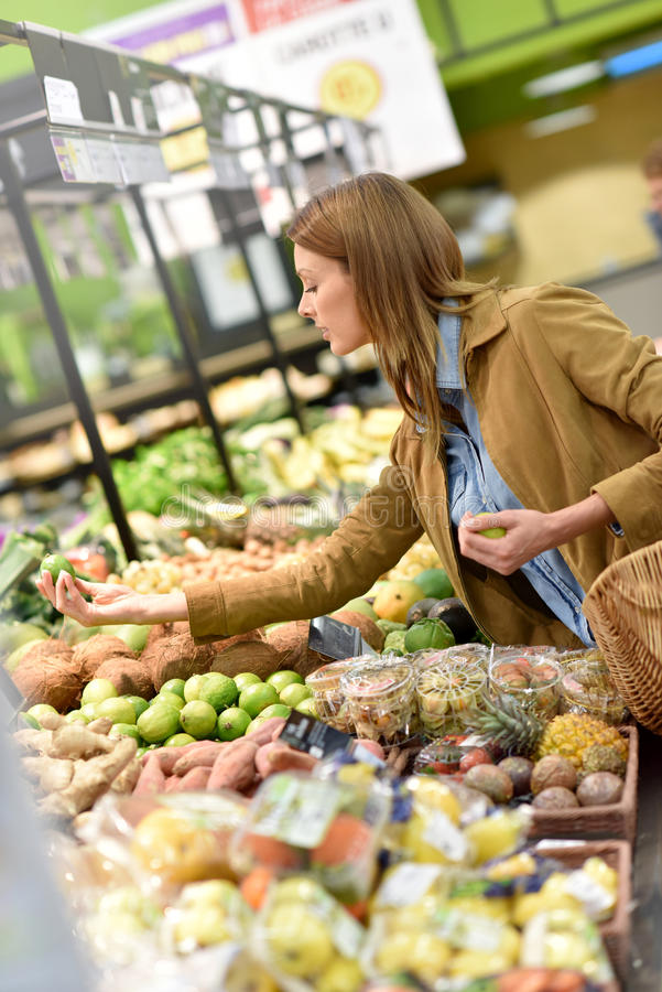 Woman at grocery store. Woman at the grocery store buying fruits and vegetables stock photography