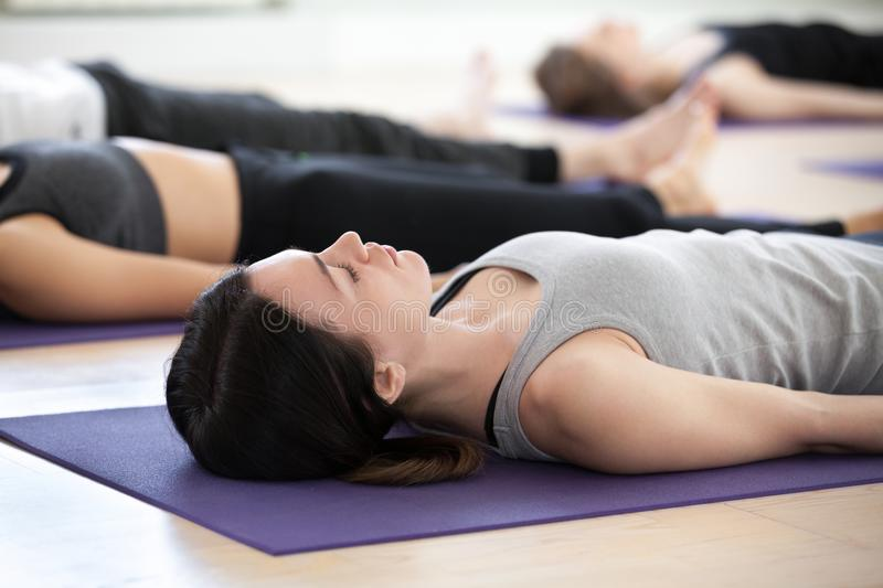 Woman and a group of sporty people in Corpse exercise. Yogi women and a group of young sporty people practicing yoga lesson, doing Dead Body, Savasana pose stock photography