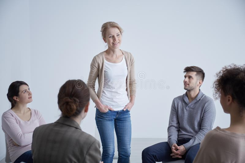 Woman in a group. Young women confessing her problem in a group stock images