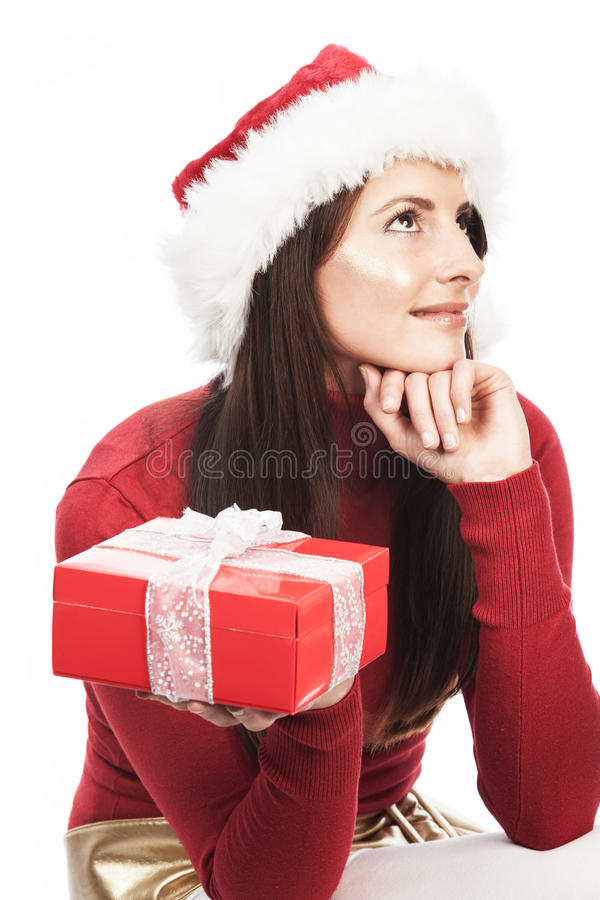 Woman guessing the contents of her Xmas gift. Woman guessing the contents of her Christmas gift in a decorative red box sitting with her chin on her hand looking stock photos