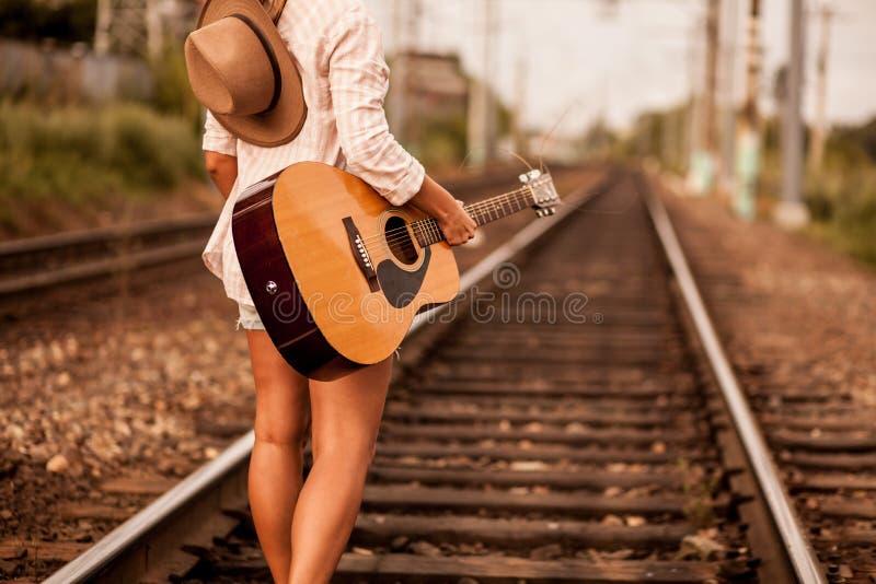 Woman with a guitar on a railway stock photos