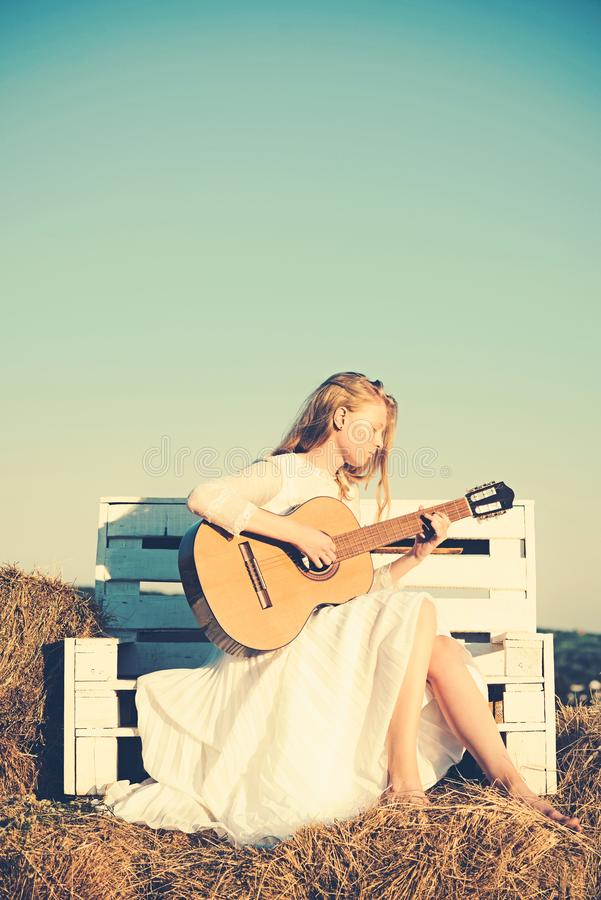 Woman guitarist perform music concert. Fashion musician in white dress on sunny nature. Albino girl hold acoustic guitar stock photos