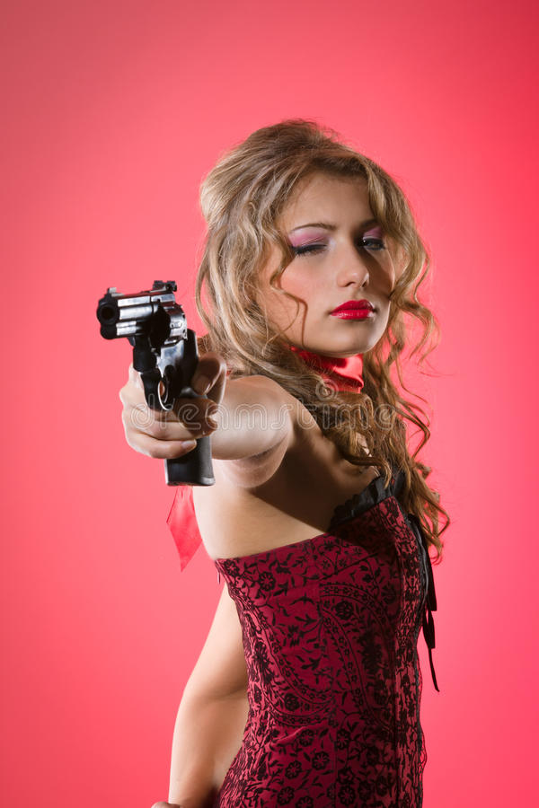 Woman and gun. Beauty girl aims with revolver form side against a red background royalty free stock photos