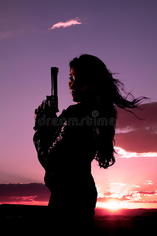 Woman gun hair blowing sunset stock photos