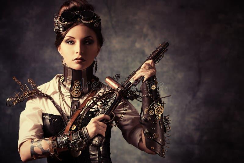 Woman gun. Portrait of a beautiful steampunk woman holding a gun over grunge background