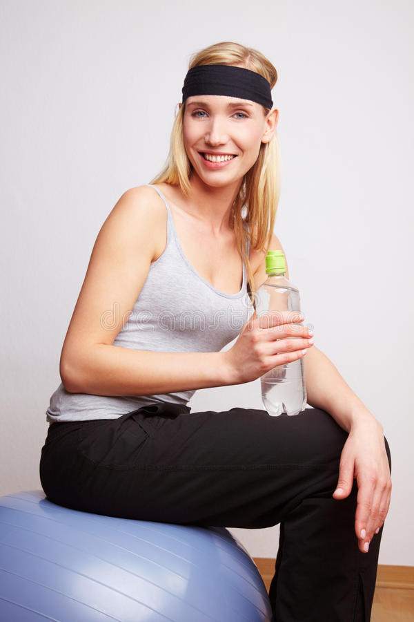 Woman on gym ball with water bottle stock photos