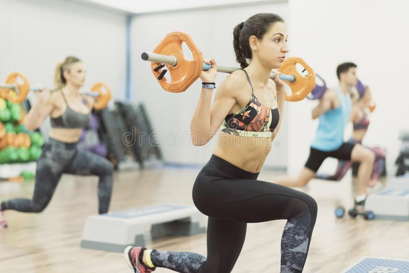 Woman in gym class training legs. And shoulder muscles wit her friends stock images