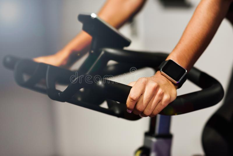 Woman at a gym doing spinning or cyclo indoor with smart watch. Hands of a woman training at a gym doing spinning or cyclo indoor with smart watch. Sports and royalty free stock images