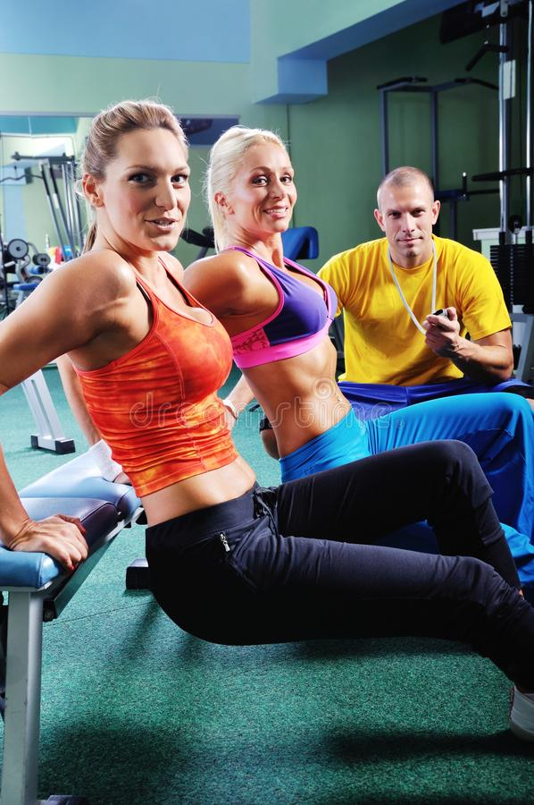 Woman in gym exercising with personal fitness trainer royalty free stock photography