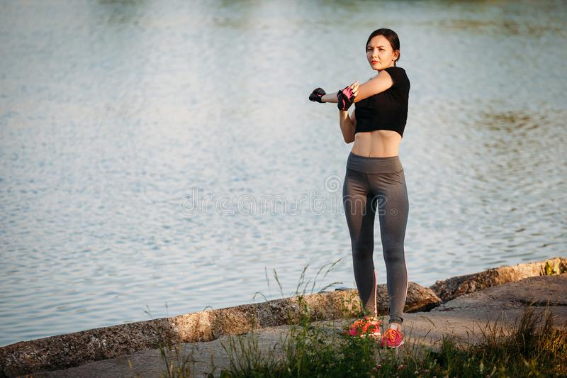 Woman gym in park. Fitness in nature. Morning exercise with beautiful, sport woman. Girl doing workout in Park stretches hand stock photography