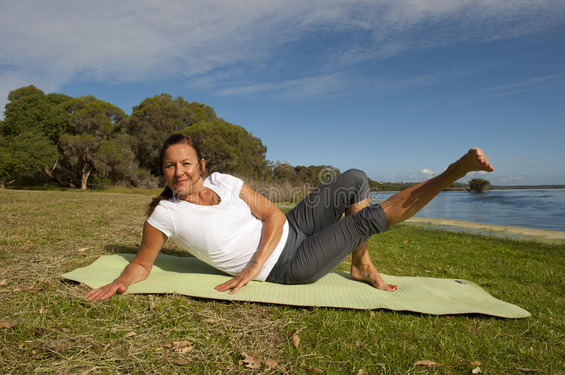Woman gymnastic exercises. Happy mature woman doing gymnastic or pilates exercises at lakeside, stretching her legs stock photos