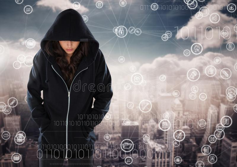 Woman hacker hooded standing on in front of digital background royalty free stock photography