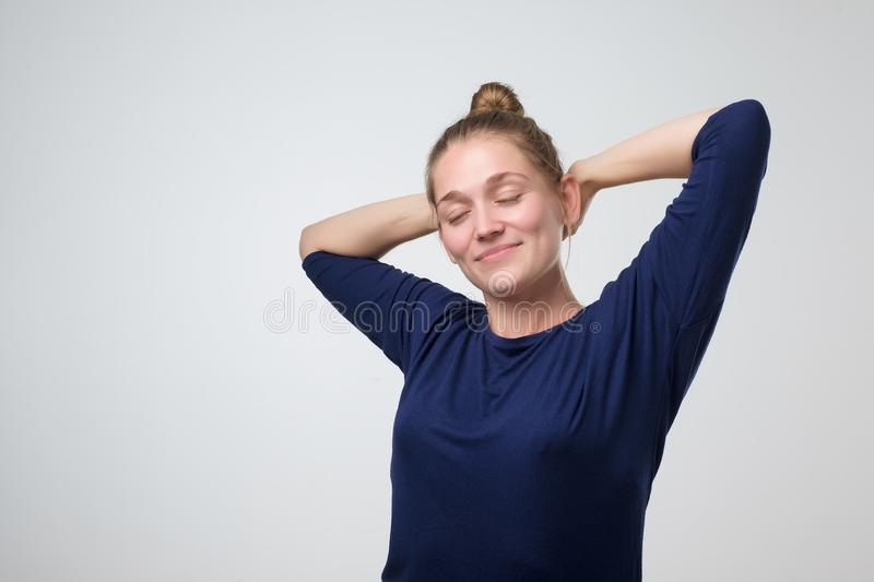 Woman with hair bun closing eyes dreaming about future. Gorgeous young caucasian woman with hair bun closing eyes dreaming about future. Resting on weekend royalty free stock images