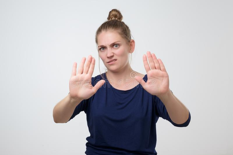 Woman with hair bun showing stop or enough gesture with hand, frowning. Unhappy caucasian woman with hair bun showing stop or enough gesture with hand, frowning stock photography