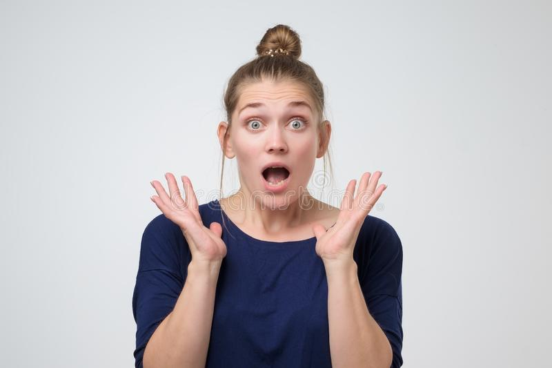 Woman with hair bun standing with open mouth shocked with the latest news. Wow concept. Beautiful surprised woman with hair bun standing with open mouth shocked royalty free stock images