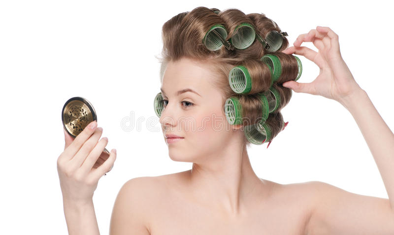 Woman in hair roller looking in mirror