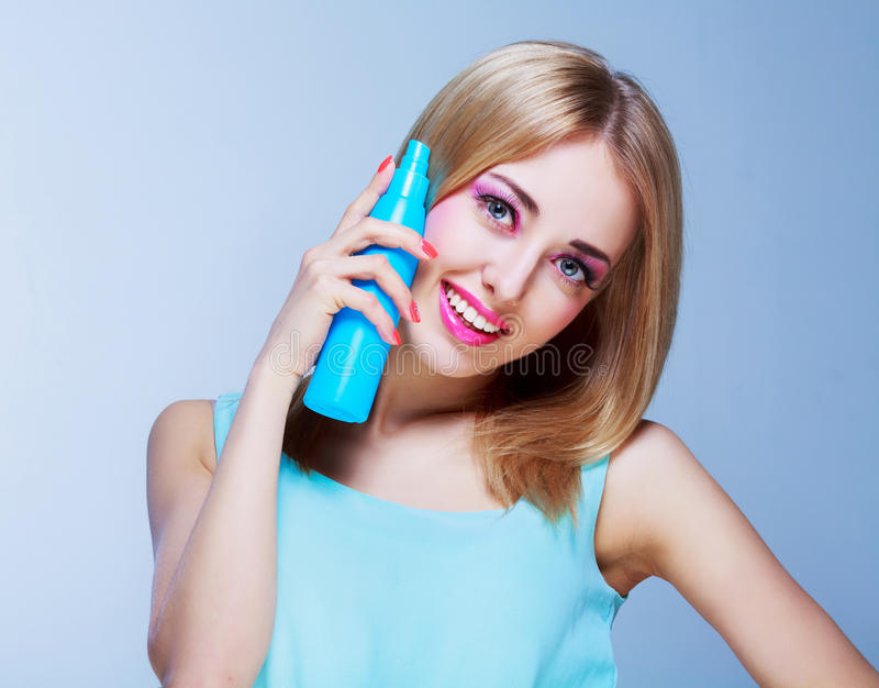 Woman with a hair spray. Pretty happy woman with a hair spray isolated against white studio background stock photography