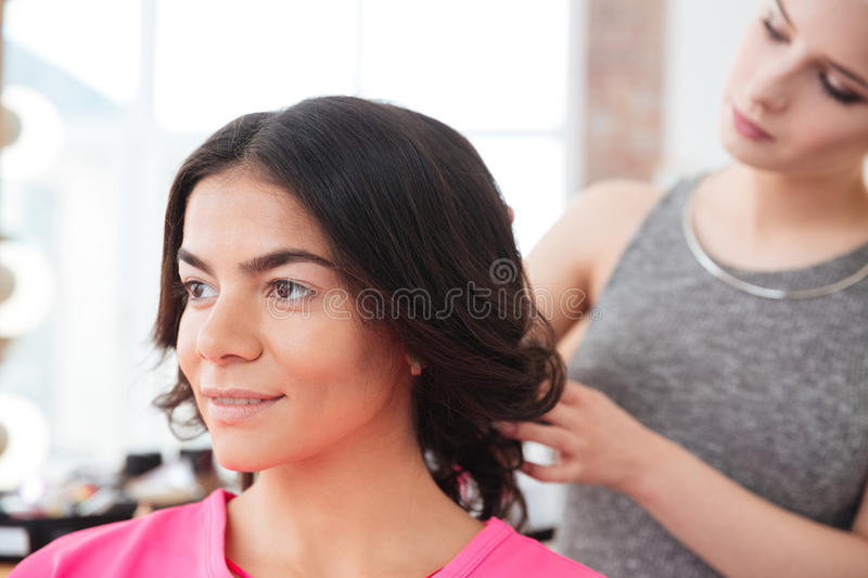 Woman hair stylist making hairstyle to young female model stock photo