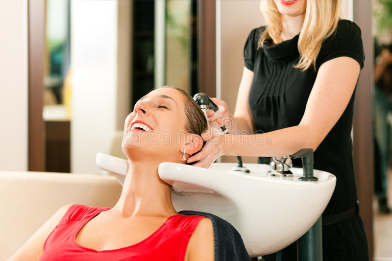 Woman at the hairdresser. Getting her hair washed and rinsed feeling visibly well stock photography