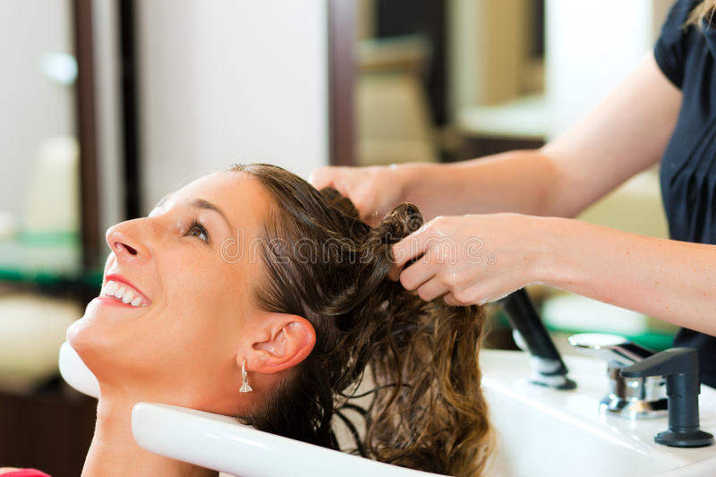 Woman at the hairdresser. Getting her hair washed and rinsed feeling visibly well stock photos