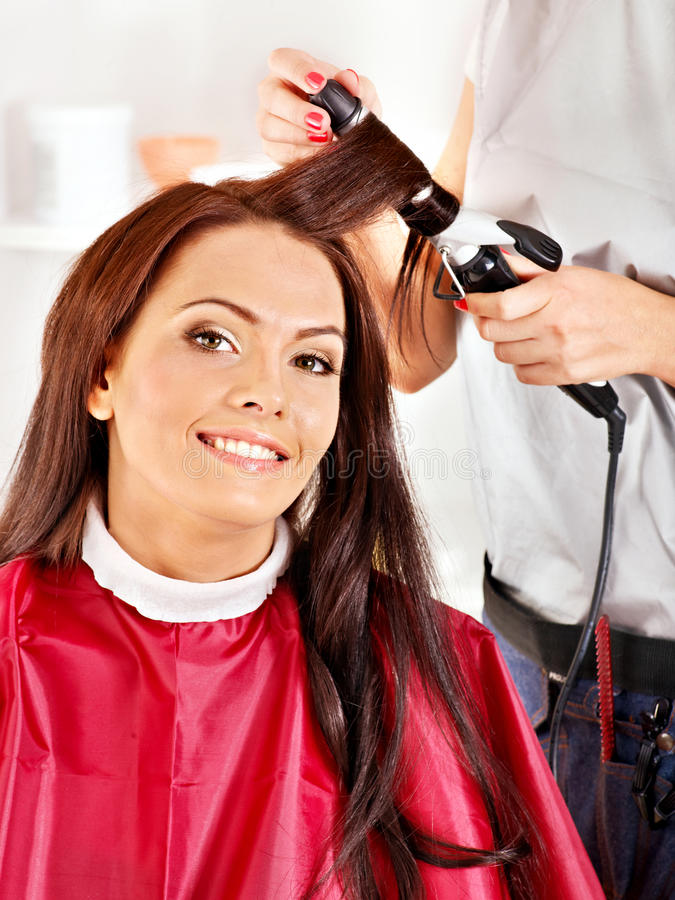 Woman at hairdresser. Woman at hairdresser with iron hair curler stock images