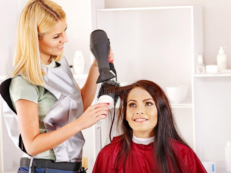 Woman at hairdresser. Woman at hairdresser with hairdryer stock photos