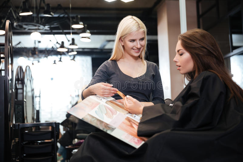Woman with hairdresser choosing hair color from palette at salon royalty free stock photo
