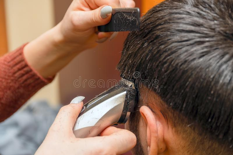 Woman Hairdresser cuts man`s hair with electric clipper trimmer. Selective focus royalty free stock photos