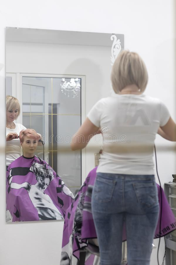 Woman hairdresser makes hairstyle in a beauty salon stock image