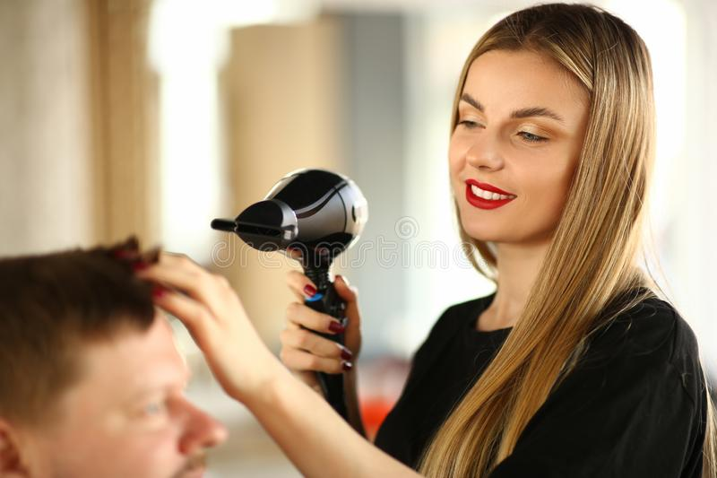 Woman Hairdresser Drying Male Hair with Hairdryer. Young Hairstylist Styling Haircut for Man with Dryer. Female Stylist Blowing on Client for Making Hairdo royalty free stock images