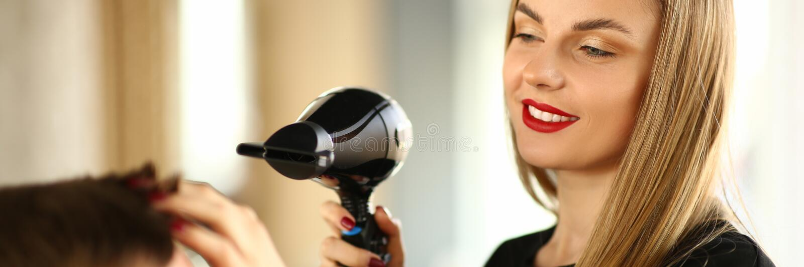 Woman Hairdresser Drying Male Hair with Hairdryer. Young Hairstylist Styling Haircut for Man with Dryer. Female Stylist Blowing on Client for Making Hairdo royalty free stock photo