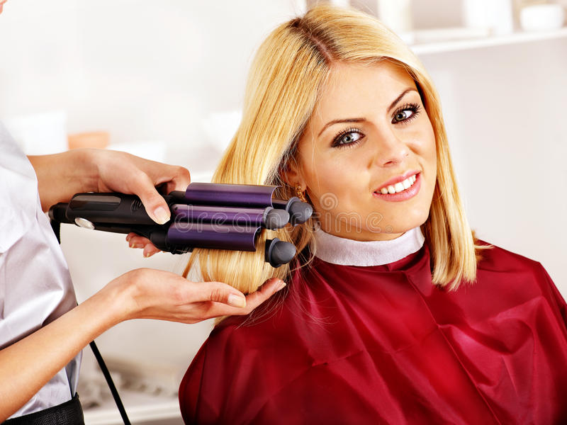 Woman at hairdresser. Woman at hairdresser with iron hair curler stock photography