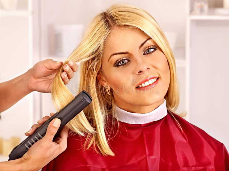 Woman at hairdresser. Woman at hairdresser with iron hair curler royalty free stock image