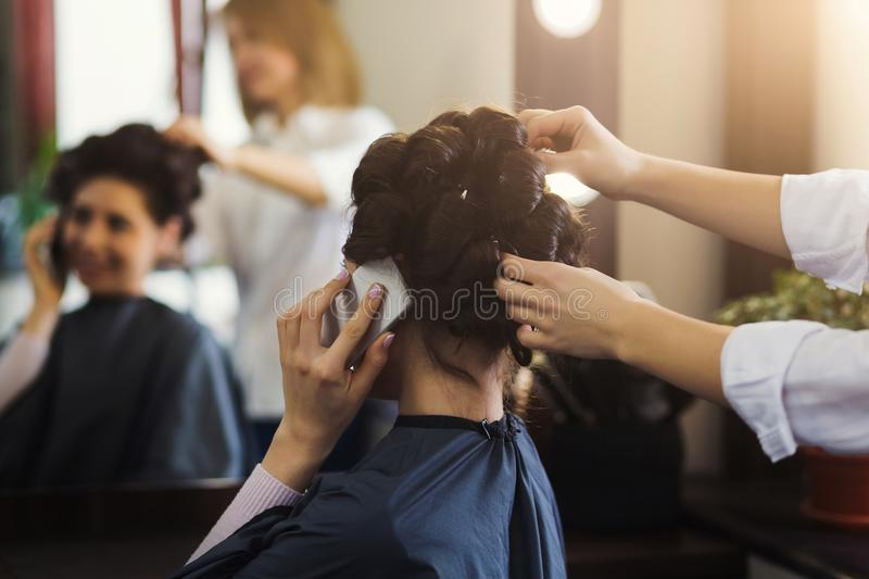 Woman hairdresser making hairstyle in beauty salon royalty free stock photos