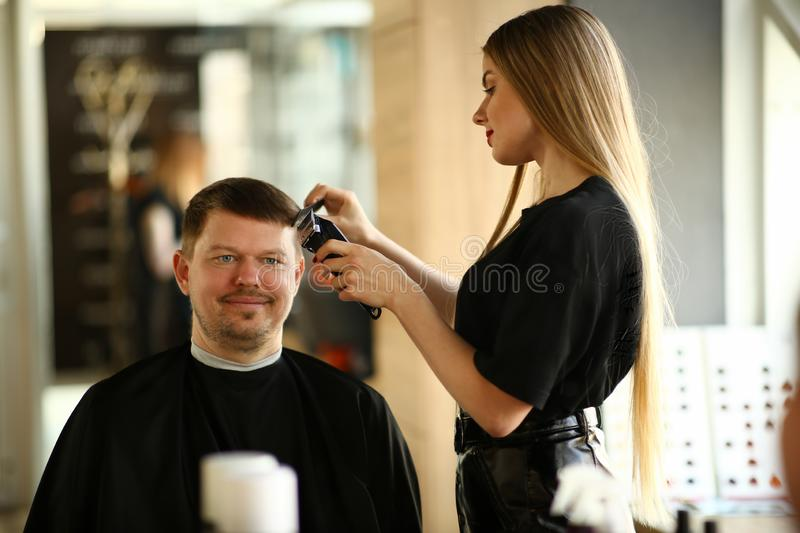 Woman Hairdresser Making Razor Haircut for Man. Female Hairstylist Styling Hairdo by Electric Shaver. Male Client Getting Hairstyle in Barbershop. Professional stock photo