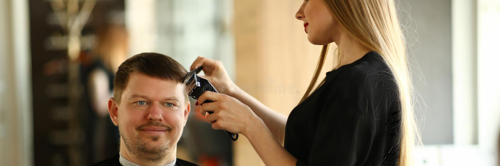 Woman Hairdresser Making Razor Haircut for Man. Female Hairstylist Styling Hairdo by Electric Shaver. Male Client Getting Hairstyle in Barbershop. Professional stock photography