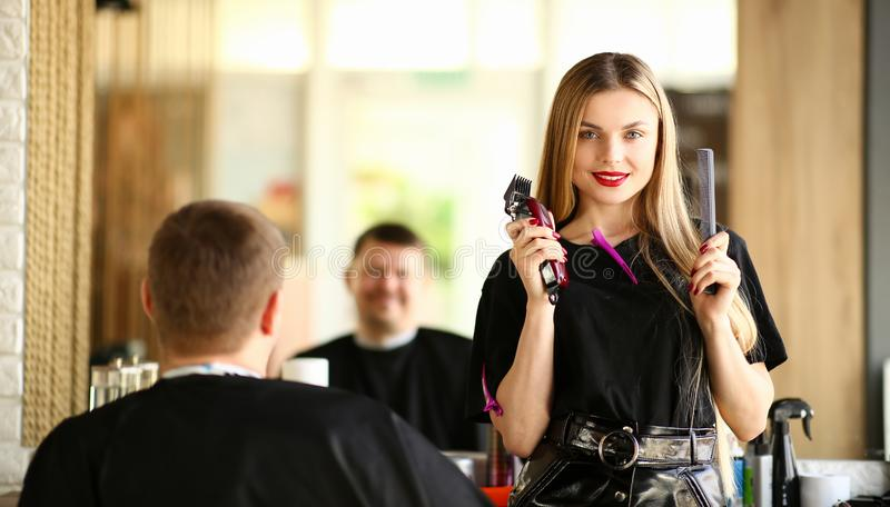 Woman Hairdresser Showing Razor and Comb to Client. Female Hairstylist Holding Electric Shaver and Hairbrush for Styling Male Haircut. Professional Stylist royalty free stock photos