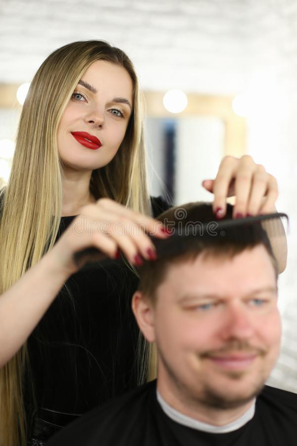 Woman Hairstylist Combing Client with Hairbrush. Hairdresser Making Haircut for Smiling Man in Barbershop. Young Girl Barber Styling Hairdo in Beauty Studio royalty free stock image