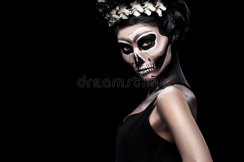 Woman in Halloween costume of Frida Kahlo with copy space. Skeleton or skull makeup. Woman in Halloween costume of Frida Kahlo on black background. Skeleton or royalty free stock photography