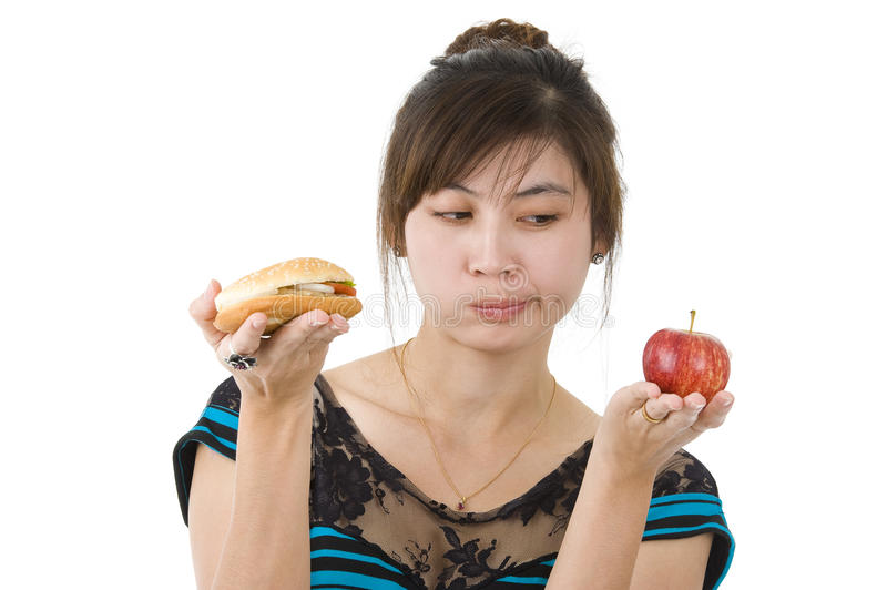 Woman with hamburger and apple. Young asian beauty with hamburger and apple, isolated on white background stock images