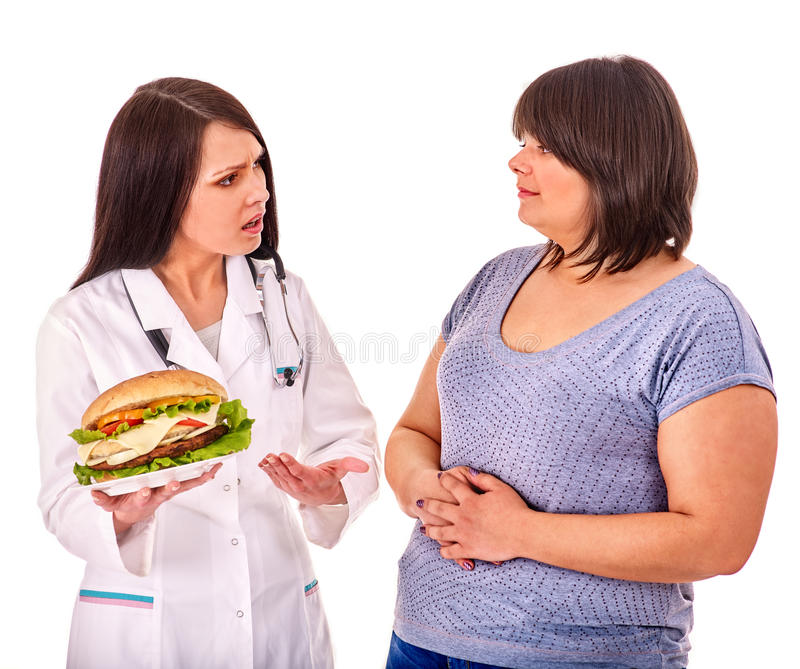 Woman with hamburger and doctor. Overweight women with hamburger . Doctor forbids eating fast food royalty free stock photos