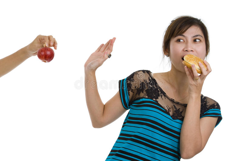 Woman with hamburger refusing an apple. Young asian beauty refusing an apple prefering a hamburger, isolated on white background royalty free stock photos
