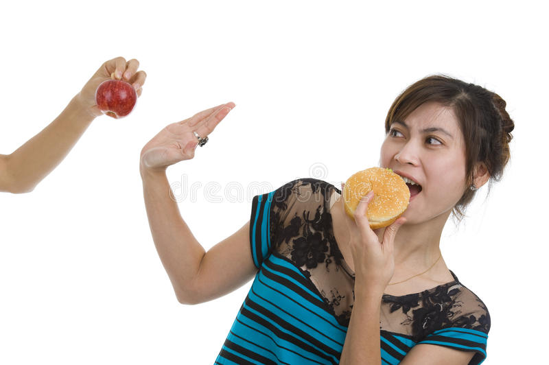 Woman with hamburger refusing an apple. Young asian beauty refusing an apple prefering a hamburger, isolated on white background stock photos