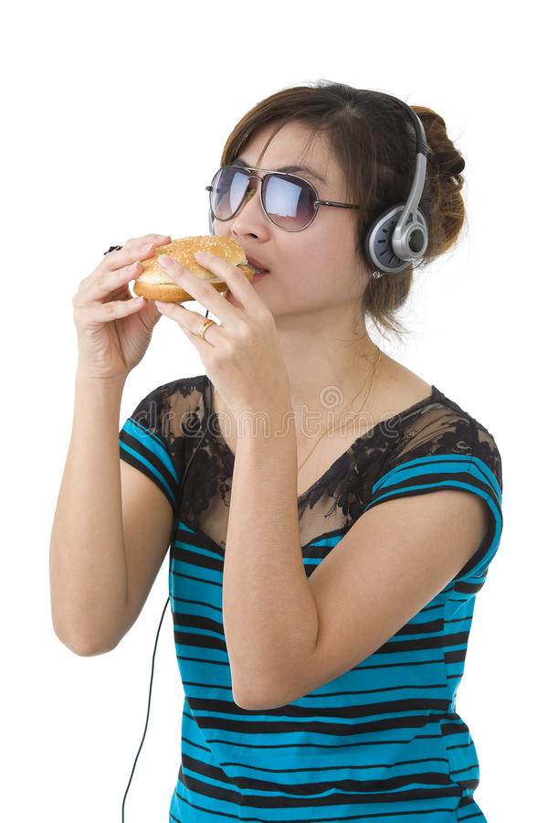 Woman with hamburger, sunglasses and head phones. Pretty woman with hamburger, sunglasses and head phones over white royalty free stock image