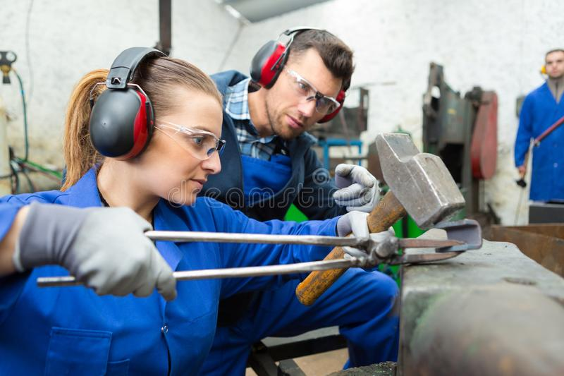 Woman hammering metal held in tongs over anvil stock photography